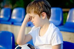 Disappointed little football fan. With ball on the stadium Royalty Free Stock Photography