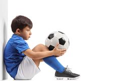 Disappointed little footballer leaning against a wall Stock Photos