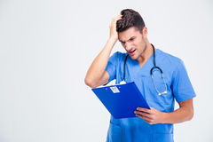 Disappointed male doctor with clipboard Stock Photo