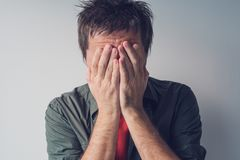 Disappointed man crying with head in hands Royalty Free Stock Images