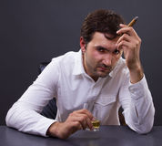 Disappointed man drunk with whiskey. Disappointed man gets drunk on whiskey and a cigar thinking of a solution Royalty Free Stock Photography