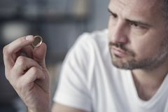 Disappointed man holding wedding ring royalty free stock photography
