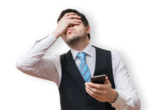 Disappointed man holds smartphone and covers his face with hand. Royalty Free Stock Photos