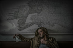 Disappointed man with a hood and empty engraved glass bottle of alcohol Stock Images