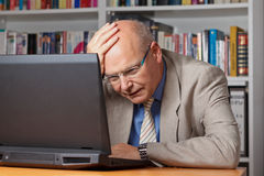Disappointed man with laptop. Elderly businessman stunned and stressed in front of his laptop Royalty Free Stock Image