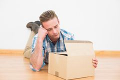 Disappointed man lying on the floor opening gift Royalty Free Stock Photo