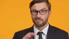 Disappointed man shrugging, looking for decision, isolated on orange background. Stock footage stock footage