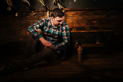 Disappointed man sits near a chest, holding glass bottle and try. Ing to get out of the trap, escape the room game concept stock photography