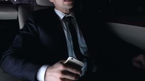 Disappointed man sitting on back seat of car and using smart phone, night city. Stock footage stock footage