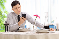 Disappointed man sitting at a restaurant. Disappointed young man sitting at a restaurant table and reading a text message on his cell Royalty Free Stock Image