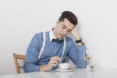 Disappointed man stirring coffee. Man sitting with head propped on the table and stirred bored in his cup of coffee royalty free stock photo