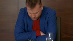 Disappointed man taking off napkin while eating tasteless meal in restaurant stock footage