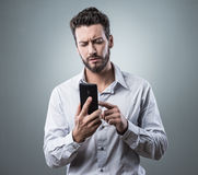 Disappointed man typing with his smartphone Stock Image