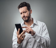 Disappointed man typing with his smartphone Royalty Free Stock Photo