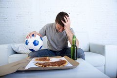Disappointed man watching football game on television sad and desperate Royalty Free Stock Photo