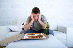 Disappointed man watching football game on television sad and desperate Stock Photos
