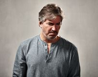 Disappointed man. Disappointed mature man over gray wall background Royalty Free Stock Photo