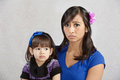 Disappointed Mother with Child. Disappointed Asian mother holding serious female toddler Stock Photos