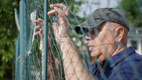 Disappointed Person Looking Hopeless Thru a Metallic Fence royalty free stock photo