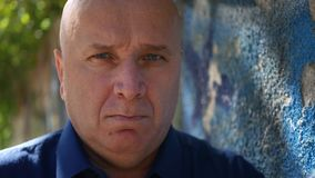 Disappointed person near a wall looking nervous and irritated to camera.  stock footage