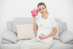 Disappointed pregnant woman shaking a pink piggy bank while holding her belly Royalty Free Stock Photography