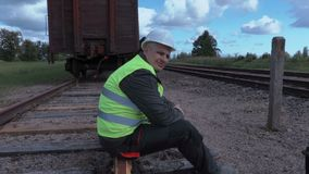 Disappointed rail worker with tablet sitting on rails. In summer day stock video
