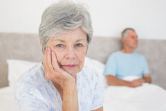 Disappointed senior woman with husband in background Royalty Free Stock Photos