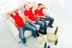 Disappointed sport fans. Three young men sitting on chouch and watching TV. They look disappointed. High angle view Stock Photography