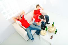 Disappointed sport fans. Three young men sitting on chouch and watching TV. They look disappointed. High angle view Royalty Free Stock Photography