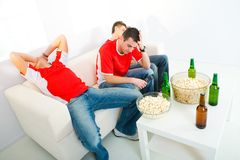 Disappointed sport fans. Three young men sitting on chouch and watching TV. They look disappointed Royalty Free Stock Image
