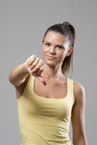 Disappointed sporty woman showing thumbs down gesture looking at camera Royalty Free Stock Photo