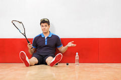 Disappointed squash player holding a broke Royalty Free Stock Image
