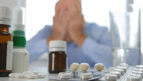 Disappointed and Suffering Businessperson With Head in Hands in Front of Pills stock photography