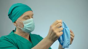 Disappointed surgeon taking off medical gloves after unsuccessful operation. Stock footage stock video footage