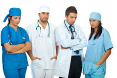 Disappointed team of doctors. Disappointed team of different doctors standing in a row and looking down or at camera isolated on white background,check also Stock Photos