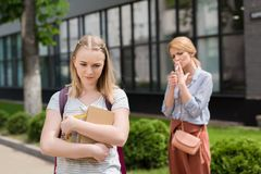 disappointed teen daughter with books looking down while her mother smoking cigarette blurred stock photo