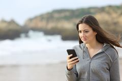 Disappointed teen reading phone message on the beach. Disappointed teen reading phone message and grimacing walking on the beach stock image