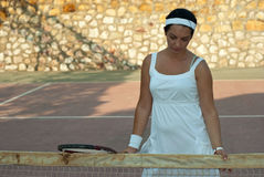 Disappointed tennis player woman. Holding racket and looking down Stock Photo