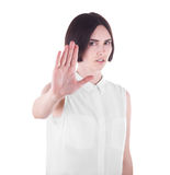 A disappointed and unpleased brunette girl with a stop gesture, isolated on a white background. A sad office lady. royalty free stock image