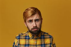 Disappointed unshaven male feels upset. Feel lonliness and sad. Has regretful expression. Dyed blonde gold hair. Isolated over studio yellow background Stock Photography