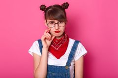Disappointed upset student standing isolated over pink background in studio, looking directly at camera, touching her face with. Fingers, wearing denim overalls royalty free stock image