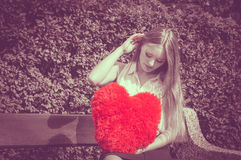 Disappointed woman with big red heart. Love and feelings. Unhappy hurt woman sitting on bench with big red heart in hands. Beautiful sad girl in park Royalty Free Stock Photos
