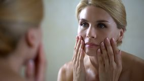 Disappointed woman looking at face reflection in mirror, anti-aging injections stock images