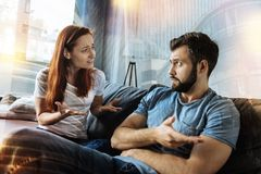 Disappointed woman looking at her boyfriend and feeling miserable. But why. Exhausted emotional young women feeling miserable and looking at her calm unfaithful stock photo