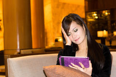 Disappointed woman. Reading news in ipad Stock Image