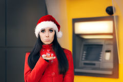 Disappointed woman with Small Gift Box in Front of an ATM. Sad girl not affording bigger Christmas presents stock image