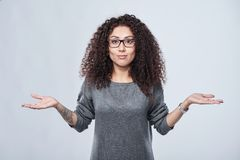 Disappointed woman with two opened hand palms. Closeup of amazed curly woman in eyeglasses with open spread hands shrugging shoulders, over grey background Stock Photos