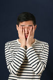 Disappointed young Asian man covering his face by palms Stock Images