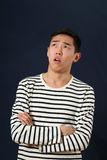Disappointed young Asian man with crossed hands looking up Royalty Free Stock Image