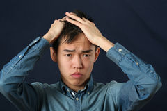 Disappointed young Asian man making face and looking at camera.  royalty free stock photography